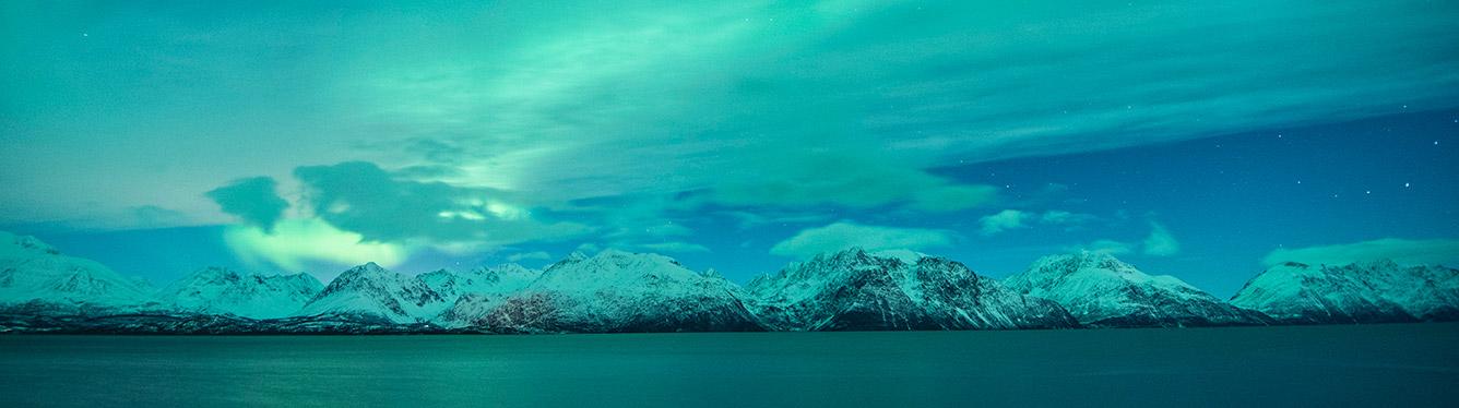 Nordlys i grønn og turkis over fjell sett fra vannet.